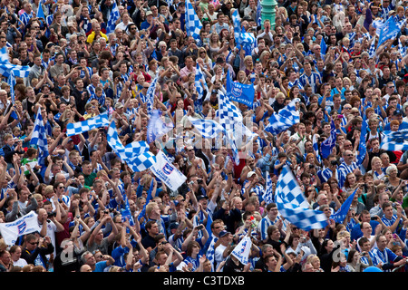 Brighton and Hove Albion Football Supporters cheer the team during the clubs victory parade along Brighton seafront. - Stock Photo