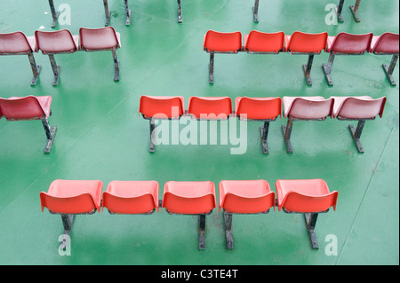 Rows of red seats on the deck of a ferry. - Stock Photo