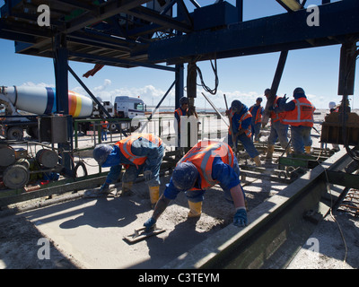 Workers pouring concrete making a new quay of the deep sea port expansion Maasvlakte 2, Rotterdam, the Netherlands - Stock Photo