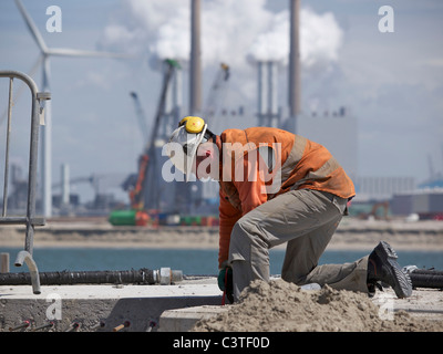 Man working at the construction site of Maasvlakte 2, with large factory in the background. Port of Rotterdam, the - Stock Photo