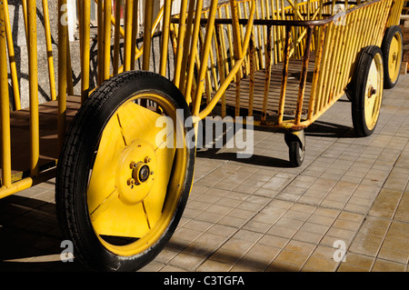 Empty yellow baggage cart detail on railway station in Rijeka, Croatia - Stock Photo