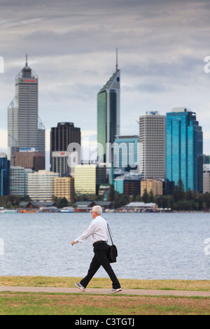Man carrying a bag and wearing trousers, shirt and running shoes on his way to work with city skyscrapers in the - Stock Photo