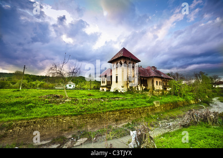 Old ruined mansion on a green meadow - Stock Photo