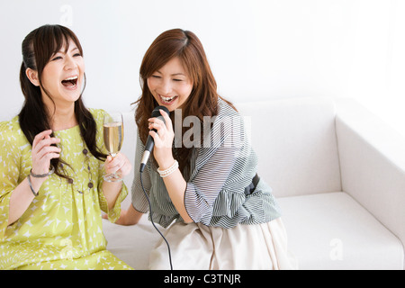 Two Women Singing Karaoke - Stock Photo
