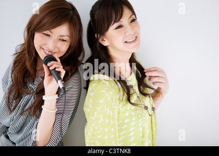 Two Women Singing Karaoke and Having Champagne - Stock Photo