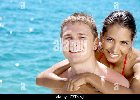Close-up of smiling girl hugging her boyfriend on the background of blue sea during holiday - Stock Photo
