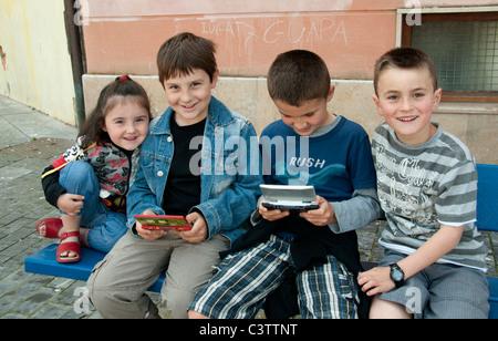 boy boys girl children playing on Nintendo handheld games Spain - Stock Photo