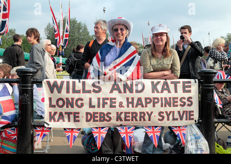 Royal Wedding fans with their banner outside Buckingham Palace the night before the Royal Wedding, April 2011. - Stock Photo