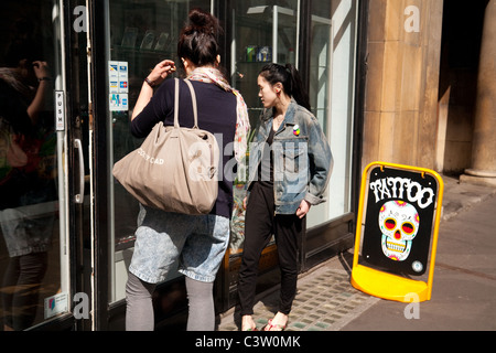 Two women looking into the window of a tattoo parlour, Cambridge UK - Stock Photo