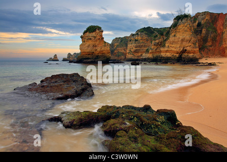 Soft morning light on the fascinating rock formations at Praia Dona Ana near Lagos in the Algarve Region of Portugal - Stock Photo