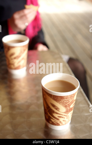 Enjoying a hot cup of tea in a take away cup outdoors on a cold day - Stock Photo