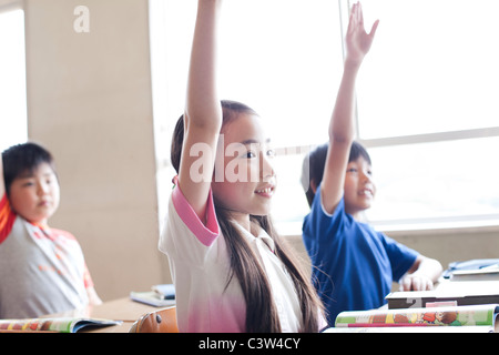 Schoolchildren Raising Hands in Classroom - Stock Photo