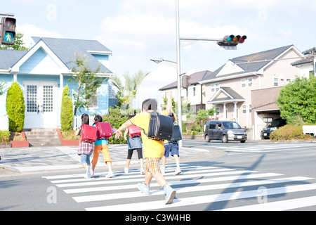 Kids crossing street, Rear View, Japan - Stock Photo