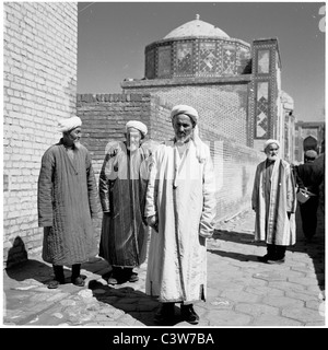 1950s. An historical picture of three elderly Uzbek men in traditional long robes outside the walls of a mosque, - Stock Photo