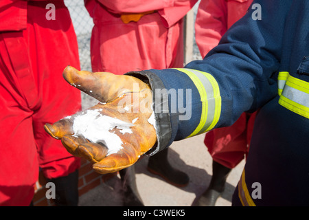 A fireman demostrates the frozen residue from a C02 fire extinguisher. - Stock Photo
