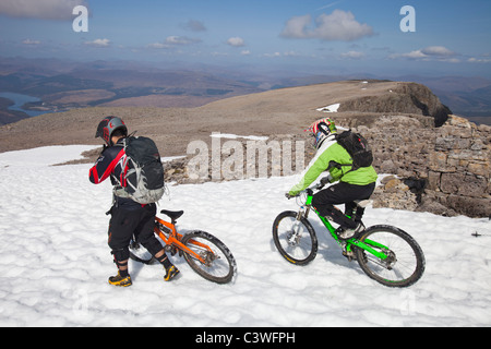 Mountain bikers descending from the summit Ben Nevis, the UK's highest mountain, Scotland, UK. - Stock Photo