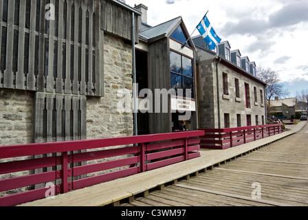Public library old flour mill at wooden entrance bridge entrance causeway to L'Ile-des-Moulins museum in village - Stock Photo