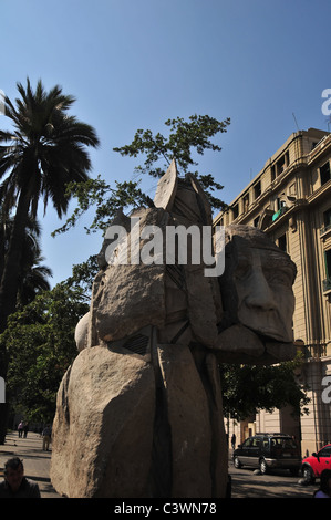 Blue sky view of large stone Mapuche Indian Monument, palm trees and buildings, Plaza de Armas, Santiago, Chile - Stock Photo