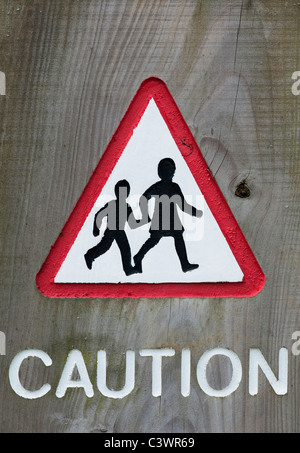 Triangular Pedestrian crossing caution sign carved into wood - Stock Photo