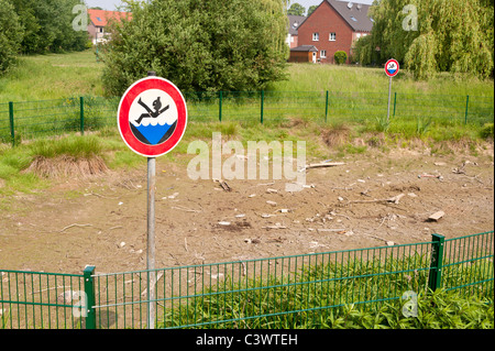 A pond is completely dry after several weeks of drought. - Stock Photo