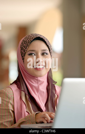 Young pretty Asian muslim woman smiles while typing notes on laptop in cafe - Stock Photo