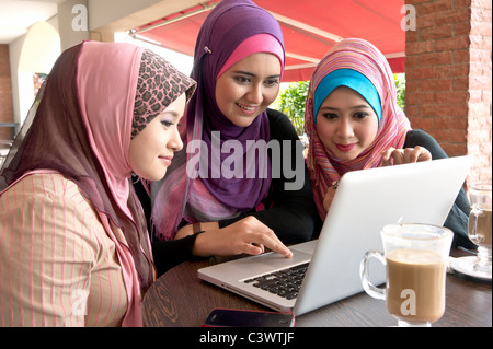 Pretty young Muslim woman in scarf having discussion using laptop in cafe with friends - Stock Photo