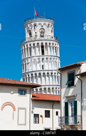 The famous Leaning Tower standing out against the sky behind the buildings of the city centre, Pisa, Tuscany, Italy - Stock Photo