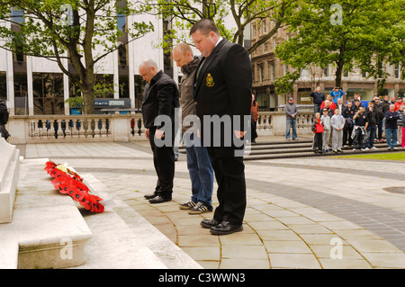 Three men lay poppy wreaths at a wreathlaying ceremony - Stock Photo