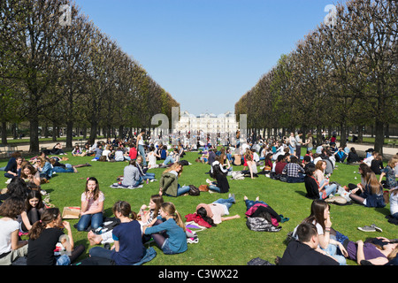 Students having lunch on lawns in front of Palais du Luxembourg in  early spring sunshine, Jardin du Luxembourg, - Stock Photo