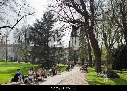Young people sitting in the Jardin du Luxembourg in the early spring sunshine, 6th Arrondissement, Paris, France - Stock Photo