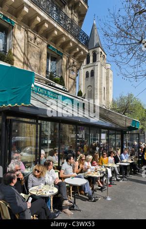 Les Deux Magots cafe on the Place St Germain des Pres with the church of Saint Germain behind, Paris, France - Stock Photo
