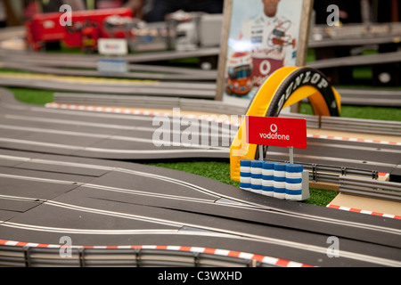 A large toy scalextric track with model cars going round the electric circuit England UK - Stock Photo