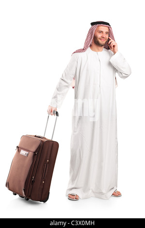 Arab tourist carrying a suitcase and talking on a mobile phone isolated on white - Stock Photo