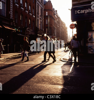 People on late Saturday afternoon in winter on the corner of Brewer and Wardour streets Soho London England  KATHY - Stock Photo