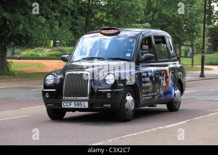 London Black Taxi Cab in Hyde Park - Stock Photo