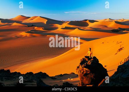 Algeria, Djanet. Sand dunes and rocks. Woman meditating. Sahara Desert. - Stock Photo
