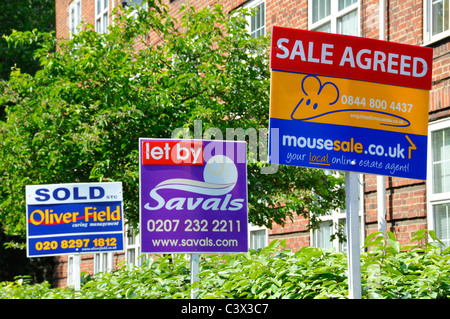 Selection of Estate Agents advertising boards for house transaction where various property has been sold let or - Stock Photo