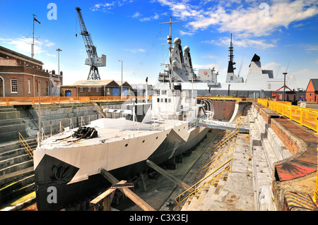 'HMS Monitor' gunship at Portsmouth dockyard Hampshire UK with two Type 45 destroyers in background - Stock Photo