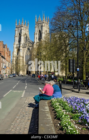 Older couple reading tourist guide in Duncombe Place with West Front of Minster in background York North Yorkshire - Stock Photo