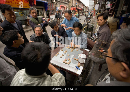 China, Shanghai, Street scenes in old city. Playing game. - Stock Photo