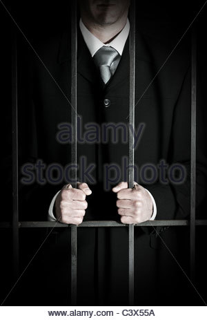 Businessman in prison cell - Stock Photo