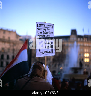Egyptians woman supporter at demonstration in Trafalgar Square holding a Socialist Worker poster supporting Victory - Stock Photo