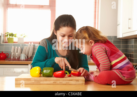 Mother and daughter chopping vegetables - Stock Photo