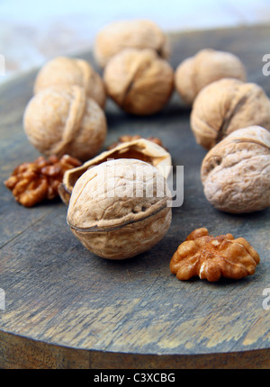 walnuts and dark chocolate on a wooden background - Stock Photo