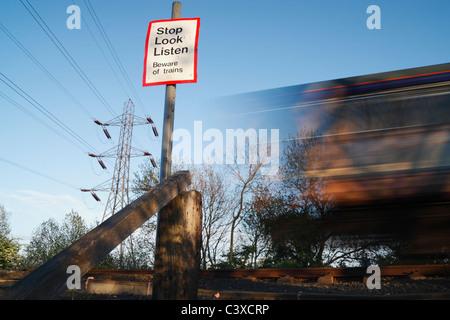 Train passing pedestrian crossing point. England, United Kingdom - Stock Photo