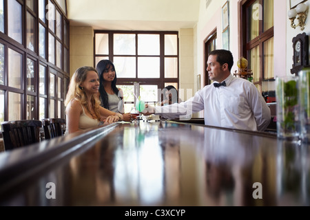 female friends sitting in pub and hispanic barman serving cocktail. Horizontal shape side view, copy space - Stock Photo