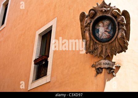 Ave Maria painting with decorated wooden frame on street corner and traditional italian house in [ Rome Italy) - Stock Photo