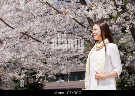 Young Woman Against Cherry Blossoms - Stock Photo