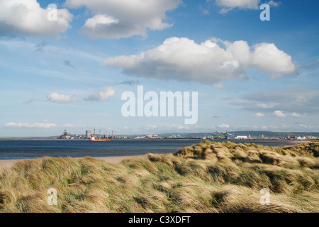 View over dunes near Seaton Carew golf course with Corus steel works at Redcar in distance - Stock Photo