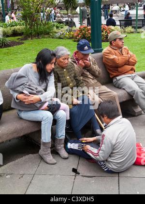 shoe shine boy and people sitting on a bench, Plaza Grande, Centro Historico, Quito, Ecuador - Stock Photo